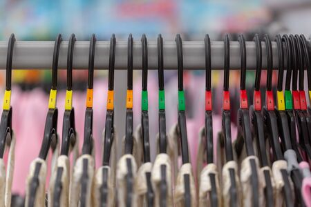 Close up of a clothing rack with hangers showing different clothing size tags.Selective focus