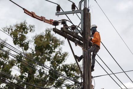 electricians repairing wire of the power line on electric power pole. Banco de Imagens