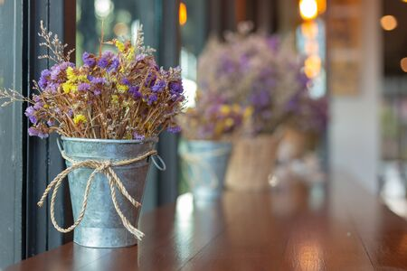 Dried flowers in a silver iron bucket decorated with coffee shops with copy space.
