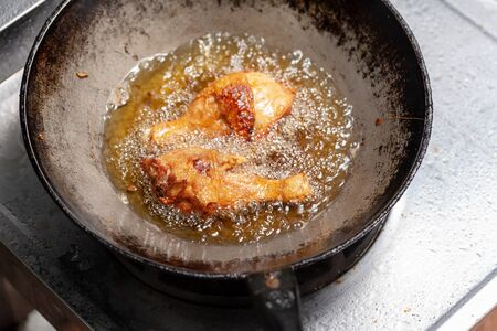 Fry the chicken in a pan with boiling oil Banco de Imagens