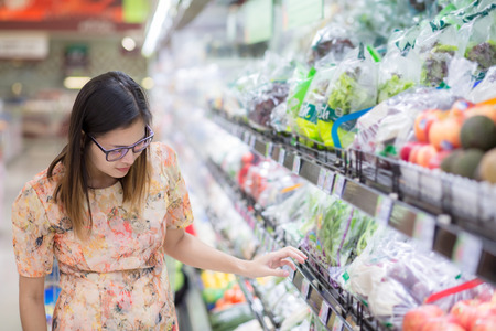 Woman in a supermarket at the shelf for fruits and vegetables shopping with copy space.