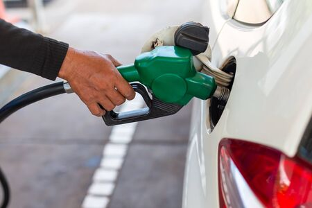 close up worker hand holding nozzle fuel fill oil into car tank at pump gas station. Reklamní fotografie