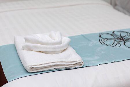 Toalla blanca en la cama en la habitación del cliente del hotel.
