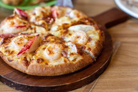 Seafood Italian Pizza slice on wood dish.