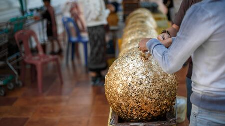 Gilding gold sheet on steel ball and Buddha statue. Religious ceremony of Thailand. Imagens