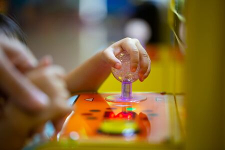The kid hand is controlling the arcade of the doll. Stock Photo