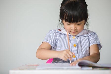 Little asian kid doing homework at home.