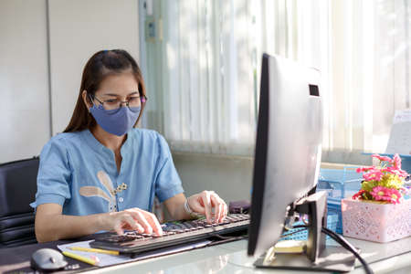 Female employee wears face mask in customer service for measures to prevent virus covid-19