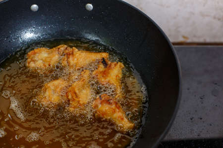 Close up fried chicken wings in boiling oil.