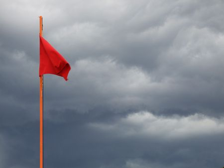 A red flag with a rainy clouds in the background Stock Photo