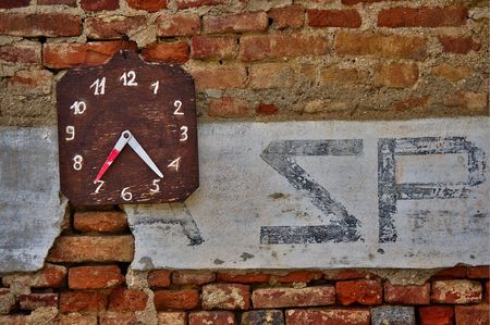 An old manual scorekeeper for the italian game of bowls in a raw bricks wall with a fragment washed-up second war slogan