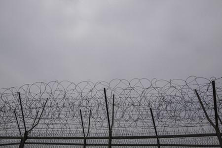 De scène van het daglicht van prikkeldraadomheining vooraan dichtbij DMZ
