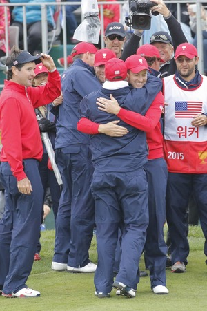pga: United States Team Player Chris Kirk and team member hug after match finished on the 18th green during the PGA Tour President Cup Single Match at Jack Nicklaus GC in Incheon, South Korea. Editorial