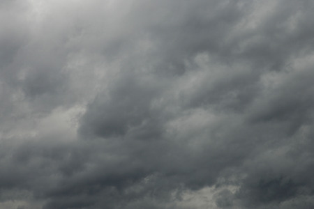 inclement weather: Sunlight peeks through dark, foreboding clouds in a violent, stormy sky. Stock Photo