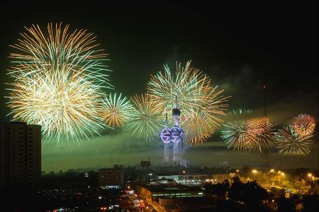Het mediaan verwerkingsbeeld van vuurwerk verlicht de hemel dichtbij de Torens van Koeweit tijdens het Festival van Hala Februari in de Stad van Koeweit.