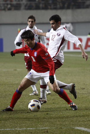 March 14, 2012 - South Korea, Seoul : Yoon Bit-garam of South Korea and Abdulla Talib S J Afifa of Qatar players compete ball during their Asia qualifying for the 2012 London Olympic in Sangam stadium. The match ended in 0-0.