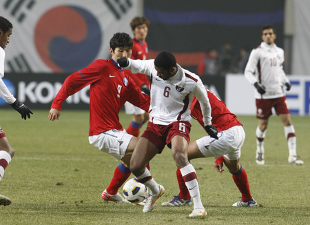 compete: March 14, 2012 - South Korea, Seoul : Kim Dong-sub of South Korea and Abdelaziz Hatim A Mohamed of Qatar players compete ball during their Asia qualifying for the 2012 London Olympic in Sangam stadium. The match ended in 0-0.