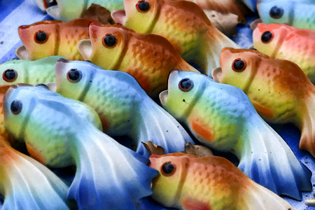 Oil painted ceramic fish displayed on the street market in thailand.