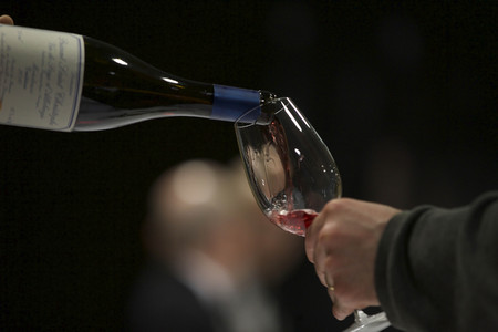 A pouring glass of red wine on a dark background. Stock Photo