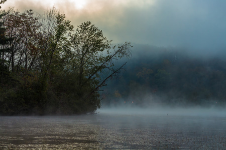 Lake with Mist in Morning with Colorful Clouds in Sky Imagens