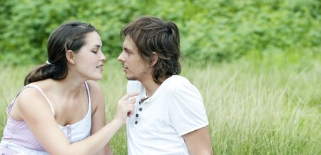Young couple in love sit in a park and enjoy the sunshine together. Stock Photo - 6520565