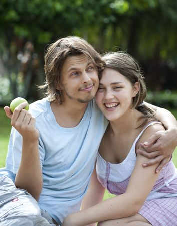 Young couple in love sharing an apple in the park Stock Photo - 6520568