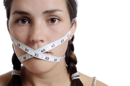 Dieting concept, cute girl had her mouth closed by measuring tape. photo