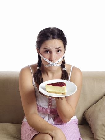 fasting: Cute girl eyes a piece of cake Stock Photo