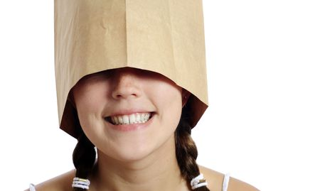 Pretty girl smiles with a paper bag on her head photo