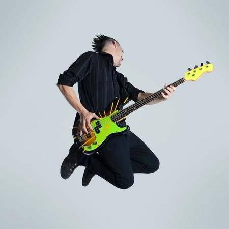 headbanging: Awesome mohawk man jumps with his guitar in studio