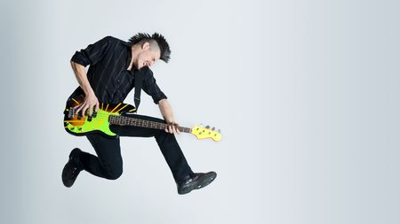 guitar player: Awesome mohawk man jumps with his guitar in studio