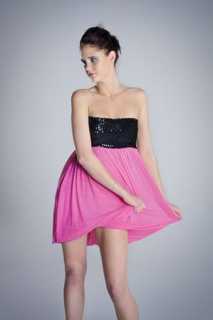 sways: Pink dress girl sways her dress and poses for the camera Stock Photo