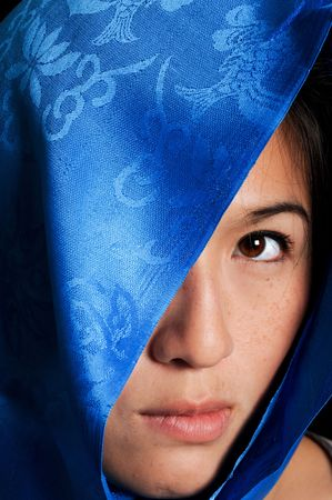 peers: Asian woman behind blue fabric peers out Stock Photo