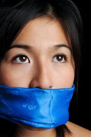 bound woman: Girl gagged with blue scarf looks for freedom Stock Photo