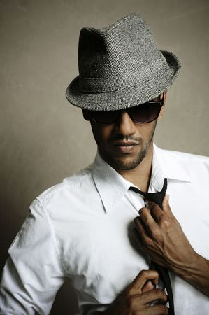 lean on hands: Fashion model shows off his tie, sunglasses and fedora