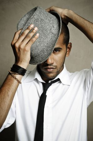 male fashion: Man poses hard as he holds his fedora Stock Photo