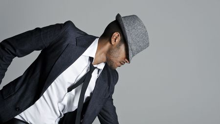 Male model poses in suit with his fedora over his face photo