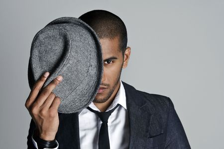 Man peeks from behind his fedora in studio photo