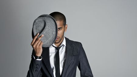 Indian high fashion model covers half his face with a fedora photo