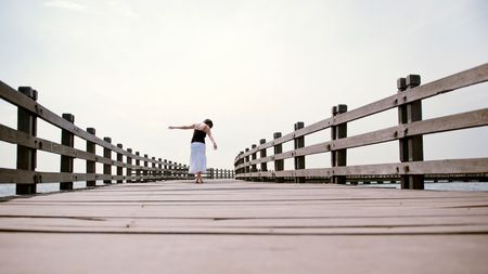Girl walks away from camera balancing on the pier photo