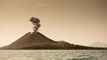 Anak Krakatau at sunset erupting onto the clear sky photo