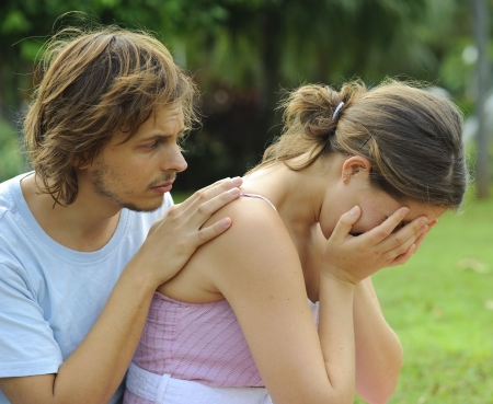 man crying: Man consoles his crying girlfriend in the park Stock Photo