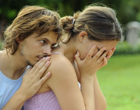consoling: Man consoles his crying girlfriend in the park Stock Photo