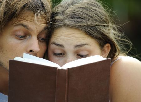 Attractive couple read together in the park photo