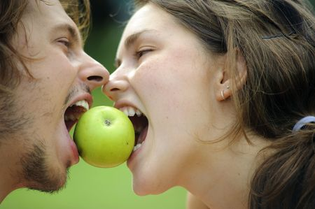 Happy healthy attractive couple with their apple in the park Stock Photo - 6677470