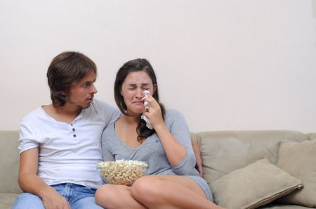 Couple watch a movie at home with popcorn photo