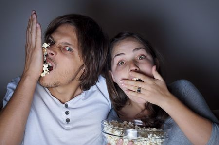 Young couple at home watching a movie with popcorn Stock Photo - 6677544