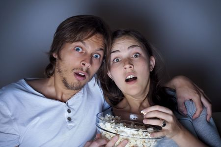 gasp: Young couple at home watching a movie with popcorn