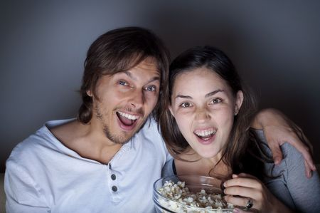 Young couple at home watching a movie with popcorn Stock Photo - 6677553