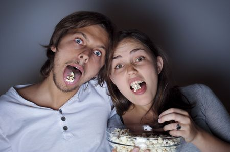 Young couple at home watching a movie with popcorn photo